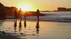 Silhouettes of friends running out the sea Stock Footage