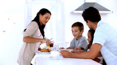 Mother pouring milk at family breakfast Stock Footage