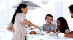 Mother chatting to children at family breakfast and pouring milk Stock Footage