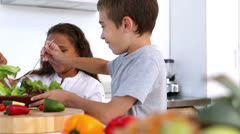 Siblings making salad together Stock Footage