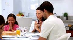 Family saying grace before dinner Stock Footage