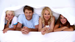 Family lying under the covers watching tv - stock footage