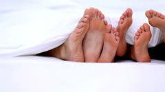 Familys feet peeking from under the covers Stock Footage