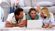 Parents and daughter happily using laptop on floor Stock Footage