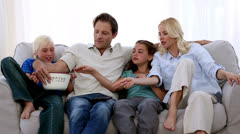 Family watching tv and eating popcorn Stock Footage