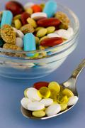 Colorful pills in bowl and spoon Stock Photos