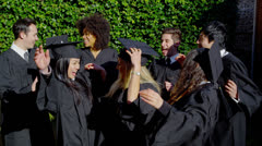 Happy multi-ethnic friends on graduation day throw their caps into the air Stock Footage