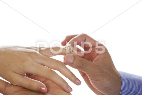 Stock photo of young adult male hand putting engagement ring on female finger
