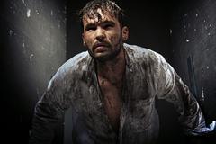 dirty man between grunge walls - stock photo