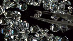 Selecting A Clear Diamond With Pincers Stock Footage