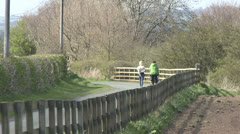 Women walk along country lane with baby buggy. - stock footage