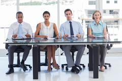 Group of business people sat in line Stock Photos