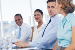 Stock Photo of Smiling business people sitting in line