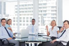 Business people looking at camera during a meeting - stock photo