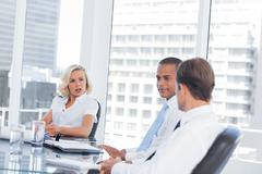 Concentrated businesswoman listening to colleagues - stock photo