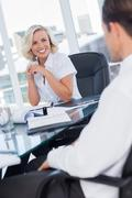Stock Photo of Smiling businesswoman listening to colleagues