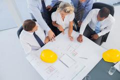 Business people working on construction plan - stock photo