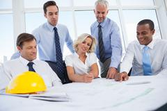 Business people discussing construction plan - stock photo