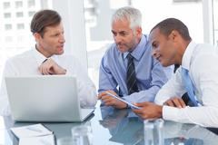 Three businessmen watching a laptop - stock photo