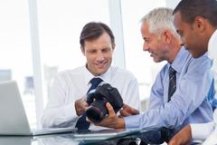 Business men interested by a camera - stock photo
