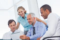 Business team watching a tablet computer - stock photo