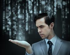 Businessman holding hand out over matrix Stock Photos