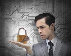 Concentrated businessman holding a padlock - stock photo
