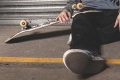 Stock Photo of Skater sitting on ground with board