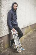 Skater leaning against wall - stock photo