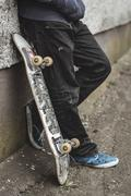 Skater leaning against wall with his board Stock Photos