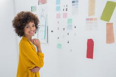 Cute designer standing in front of material samples - stock photo