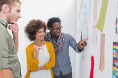 Smiling team of designers pointing at a wall Stock Photos
