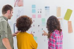 Team of designers working together and pointing at a wall Stock Photos