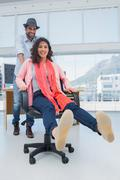 Creative business team having fun on a swivel chair - stock photo