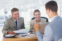 Smiling business people laughing with applicant - stock photo