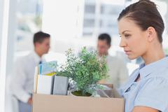 Annoyed businesswoman leaving office after being let go - stock photo