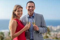 Delighted couple clinking champagne Stock Photos