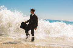 Stock Photo of Businessman walking at the edge of the sea