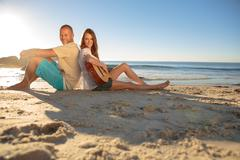 Happy couple sat back to back on the beach Stock Photos