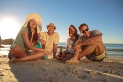 Laughing friends partying on the beach with beers - stock photo