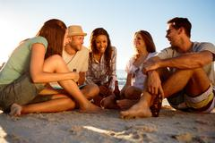 Friends partying on the beach with beers - stock photo