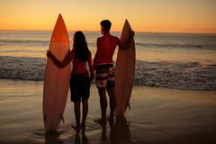 Couple hand in hand holding surfboards on the beach - stock photo