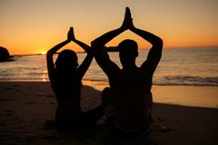 Silhouettes of people practicing yoga sat on the beach - stock photo