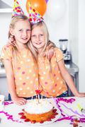 Stock Photo of Twins looking at the camera on a birthday