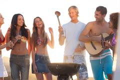 Stock Photo of Happy friends preparing barbecue on the beach