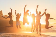 Stock Photo of Young people jumping in front of the sunset