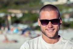 Attractive man wearing sunglasses on the beach Stock Photos
