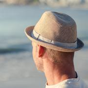 Relaxed man with a hat on the beach - stock photo