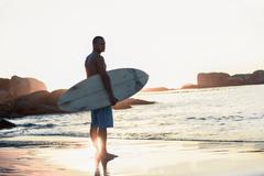 Handsome man holding surfboard - stock photo