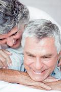 Cheerful retired couple lying together - stock photo